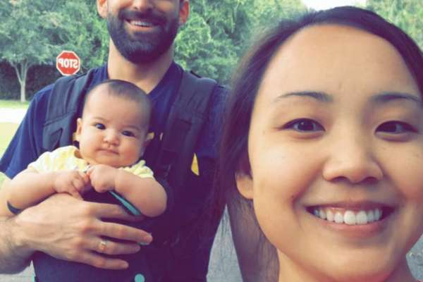 Doctor Dan Cohen spending time with his wife and child. His wife is taking a selfie of the three of them and Dan is wearing the baby in a carrier on his chest..