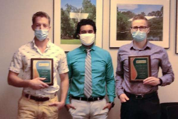 Doctor Grajo presents research award plaques to residents Parker Merritt and Jerry Slater