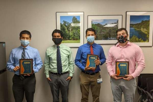 Doctor Joseph Grajo presents plaques to research week award winners Doctors David Alvarez, Edmond Olguin, and Joseph Zachary