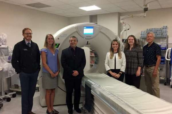 Medical Physics faculty stand in front of CT scanner